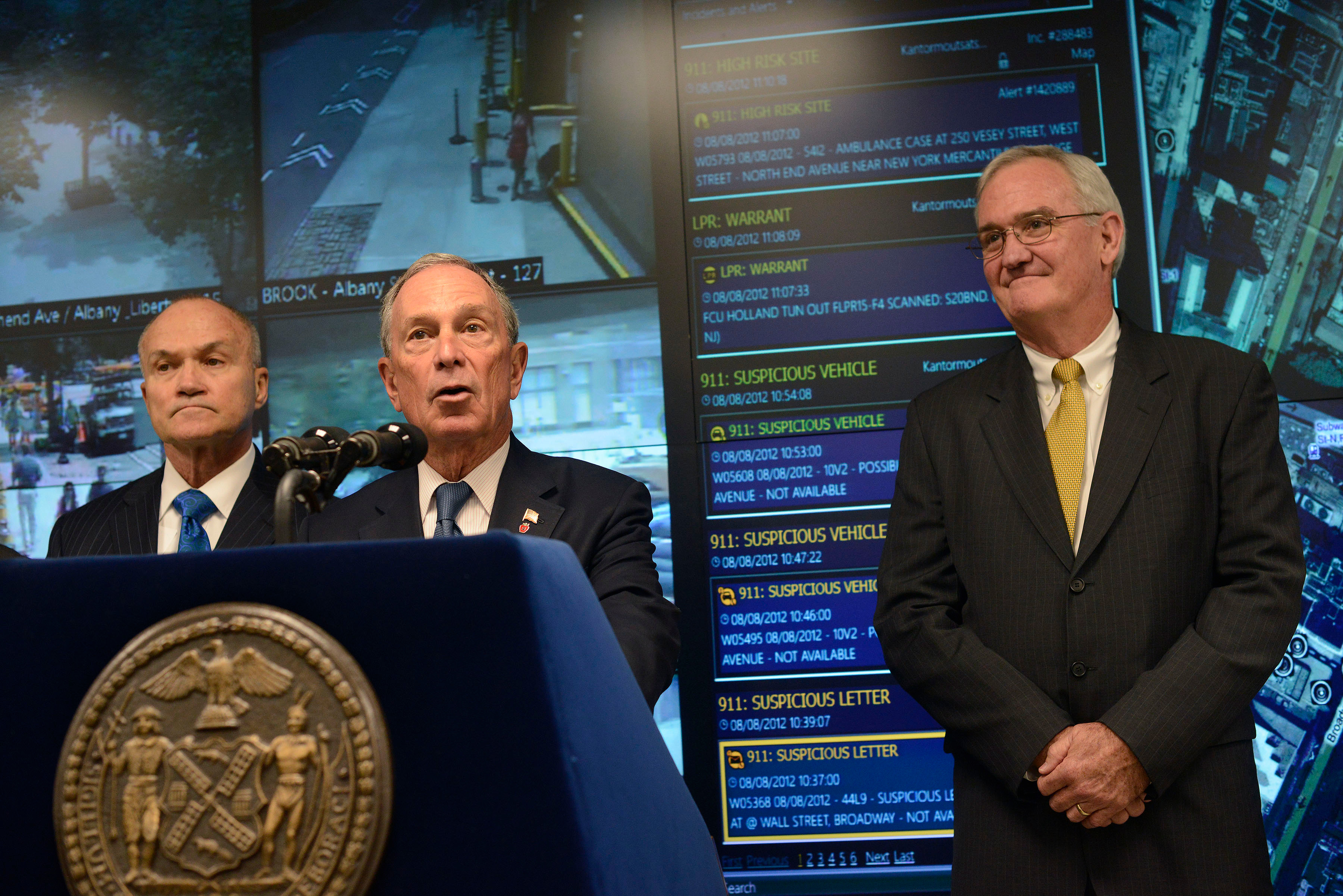 New York City Police Commissioner Raymond Kelly(L) and Microsoft Vice President of Americas Services Mike McDuffie(R) listen as New York City Mayor Michael Bloomberg speaks during a news conference in New York