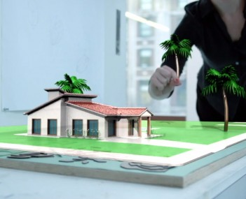 A Meta rendering shows a wearer adjusting 3-D landscaping in front of a virtual building.