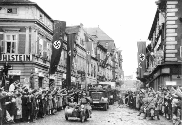 German mechanized troops enter Saaz. The streets are decorated with swastika flags and banners. 9.10.1938 14.30 Uhr. Saaz. Sudetenland