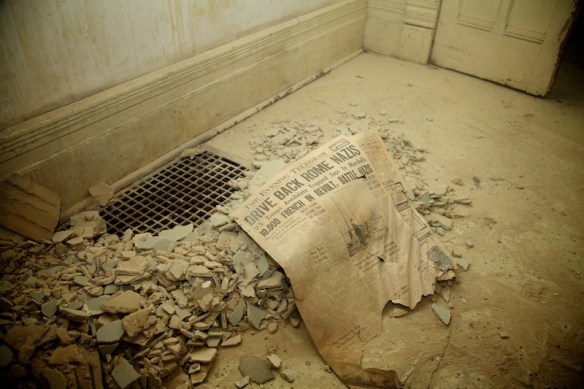 Newspaper clipping and rubble in derelict house.  (c) Allyson Scott