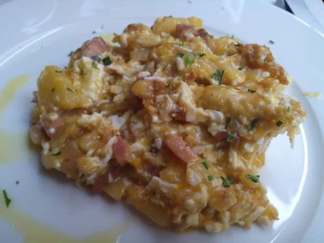 Huevos rotos con patatas, cebolla y beicon