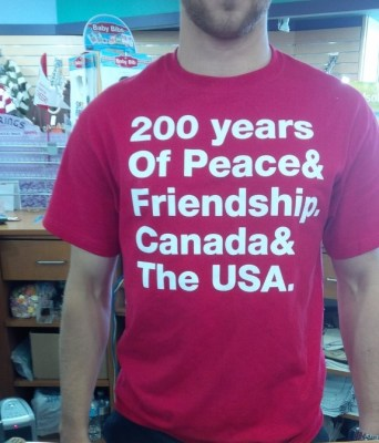 """An image of store staff wearing a t-shirt saying """"200 years of Peace & Friendship, Canada & the USA"""""""