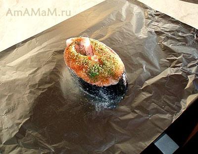 Стейк лосося, выложенный на фольгу и посыпанный пряными травами. Ожидает, пока его запеленают в фольгу.