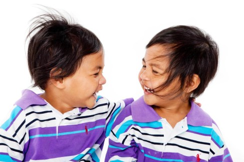 Portrait of twins laughing and looking at eachothers professional studio photography by Anais Chaine in Auckland Ponsonby New Zealand