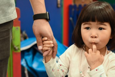 Young girl with her fingers in her mouth holding her father's hand