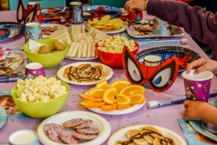 Fod on the birthday table : cakes, oranges, pop corns, spider man mask, sandwiches