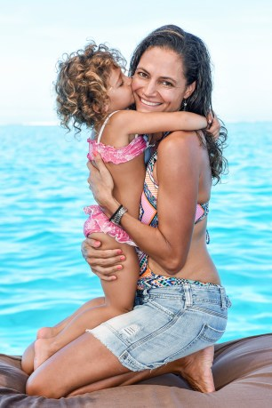 The litle girl kisses her mom aboard Cloud 9 at Fiji