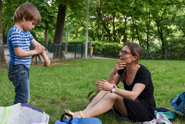 young boy showing an insect on his arm to his mum in the park