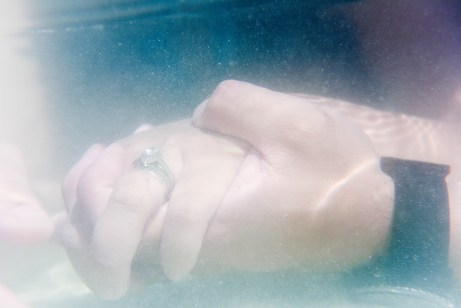 underwater photography of a couple holding hands with the engagement ring in Fiji by Anais Photography