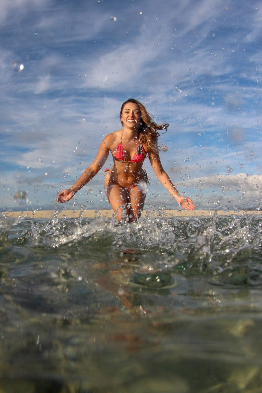 Woman trowing water to the photographer in the sea