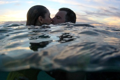 Couple kissing over the water at sunset in Fiji