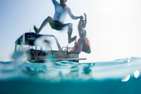 Couple jumping in the pacific ocean for their underwater photoshoot