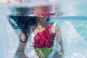 bride holding her bouquet under the water in Fiji by Anais Photography