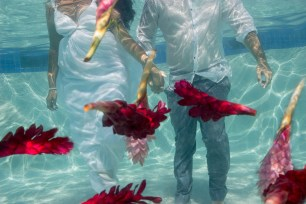 couple holding hand underwater with flowers floating in the swimming pool at the Westin resort in Denerau Fiji