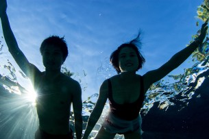 asian couple in the swimming pool of Tokoriki from underneath while they are swimming