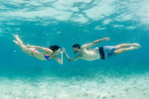 Couple reaching towards each others underwater Cloud 9 in the Mamanuca islands in Fiji