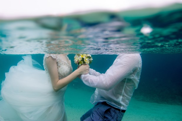Couple holding hands and flowers underwater in Fiji for their trash the dress photoshoot