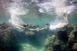 Couple swimming underwater for trash the dress photoshoot in Fiji