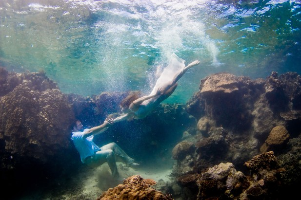 Couple swimming underwater by a coral wall