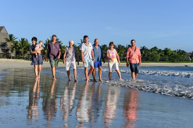 3 generations of family stroll in the ocean at Natadola beach Fiji