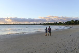 Mom dad and daughter walk down the sandy beach of Natadola in Fiji