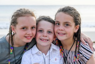 Cute brothers and sisters smile on family photoshoot beach in Fiji
