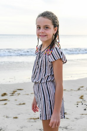 Cute young girl with braids poses by Fiji beach