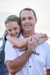 Braided daughter hangs on daddy's shoulder in family beach photography