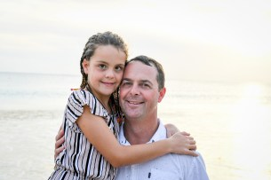 Daddy and daughter hug on beach in Fiji