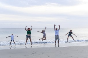 Family jumps in the air on the beach in Natadola Fiji