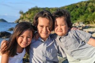 3 cute siblings do cute sidehug while posing on the beach during their family photoshoot