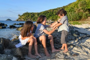 Brother tickles brother and sister laughs on the beach in family photo session Fiji