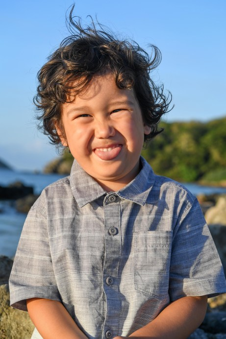 Cute curly haired boy sticks out his tongue at the beach in Malolo Fiji