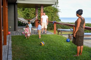 Triplets play with their dad during the Fiji family vacation
