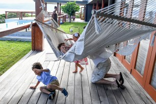 Triplets and dad play on hammock during Fiji family vacation