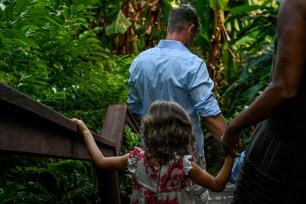 Dad and daughter walk on bridge into tropical forest during family holiday in Fiji