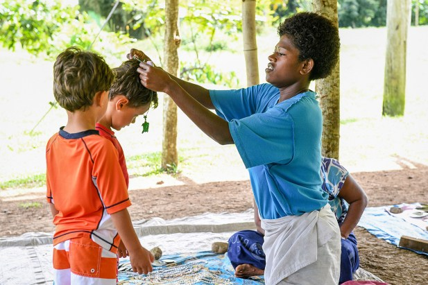Fiji woman puts traditional Fiji necklace on boy