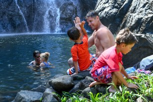 Son high fives dad at Fiji river