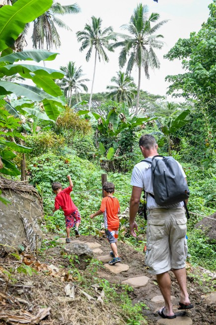 Family walks back through tropical rainforest in Fiji