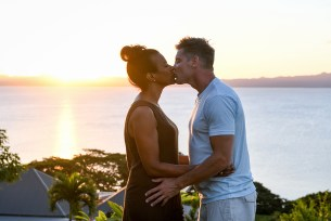 Mixed race caucasian and Polynesian couple kiss against sunset and the ocean in Fiji