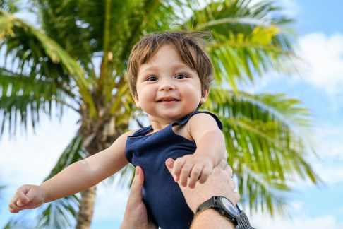 A cute caucasian baby is lifted up against a palm tree