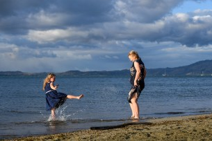 A girl kicks water at her mother at the beach at Denarau Fiji