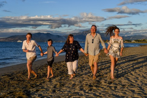Family holds hands on the beach at Denarau Fiji