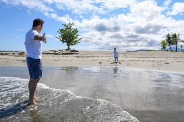 A father waits with open arms for his son while standing on the beach