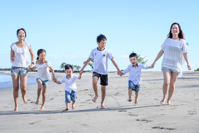 Cute asian family hold hands and run on the beach at Natadola Fiji