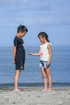 A sister shows her brother a shell she picked on the beach