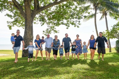 The extended family holds hands while on manicured Fiji grass