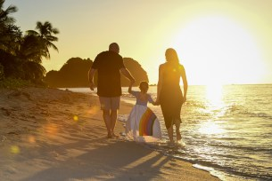 A fiery sun sets on the family as they stroll on the beach