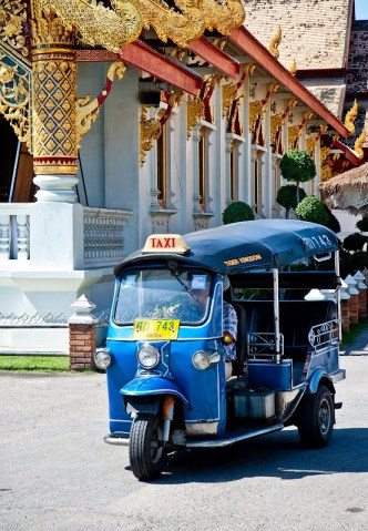 blue tuk-tuk taxi stopped in front of a temple in Chiang Mai