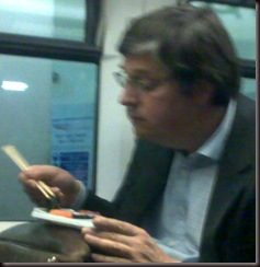 man eating sushi on train